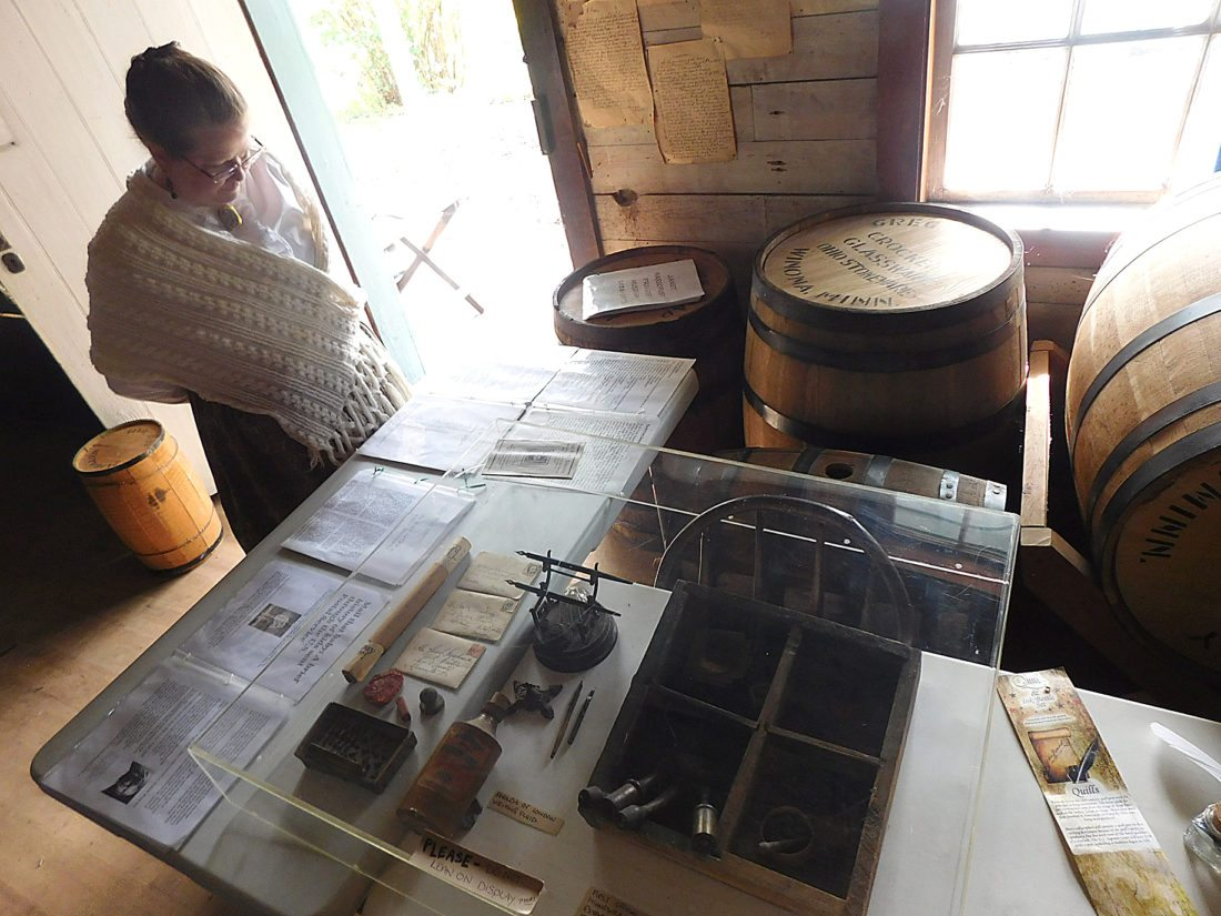 Harkin Store Site Manager Ruth Grewe stands by a variety of antique artifacts and letters on display during a program on the history of the West Newton Post Office Sunday at the Harkin Store.