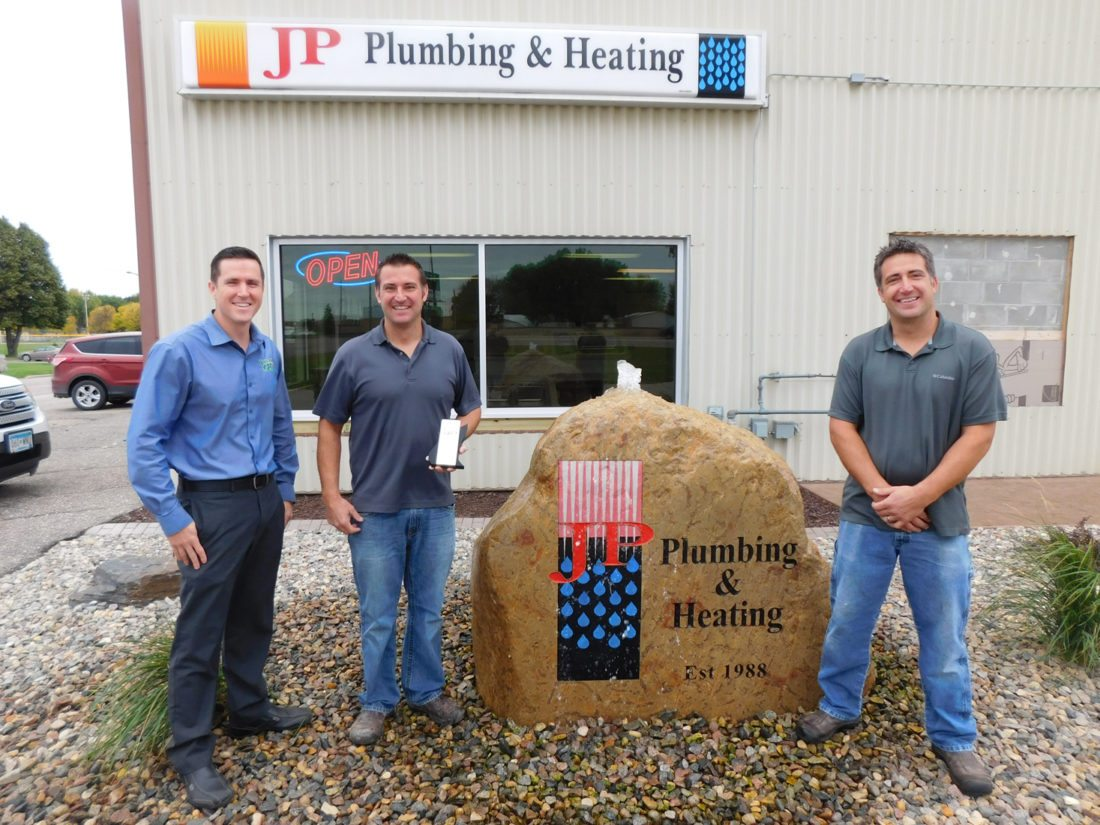 Staff photo by Clay Schuldt  From left, Eric Spies, Scott Dreckman and Seth Dreckman stand with the 2016 Distinguished Dealer Award, outside the store.