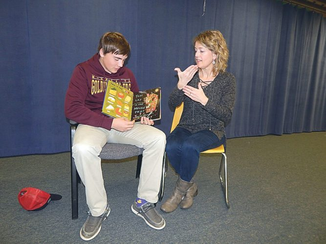 """Staff photo by Fritz Busch New Ulm High School sophomore Ben Arnoldt reads a book while his mother Terri Arnoldt tells the story in sign language at the """"A House for Me"""" program at the New Ulm Public Library Saturday. The event included NUMAS Haus volunteers and friends supporting National Hunger and Homeless Awareness Week and Give to the Max Day."""