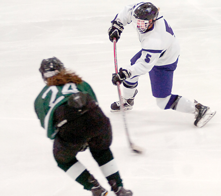 Staff photo by Steve Muscatello New Ulm's Ali Beltz (5) launches a shot on goal as Olivia Williamson of Faribault looks on during the first period Tuesday a the New Ulm Civic Center. For more photos of this event go to cu.nujournal.com