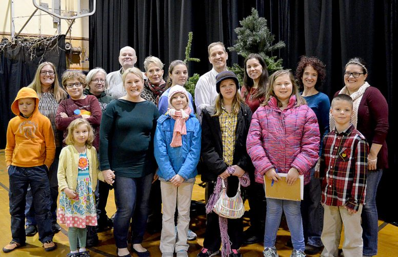 """Staff photo by Connor Cummiskey The carolers and actors in """"Tannenbaum Tales,"""" to be performed Friday and Saturday Nov. 24 and 25 stand backstage in front of two Christmast trees. Pictured left to right, front row: Edwin Hendrickson, Aidan Hendrickson, Ivrin Hendrickson, Ivy Harrison, Jayda Schewe, Hailey Schewe, Elissa Ries and Isaac Schewe; back row: Emily Edel, Brenda Nielsen, John Bergstrand, Bonnie Lantz, Makaila Schewe, Aldean Hendrickson, Anita Prestidge, Nita Gilbert and Jenny Spurgin."""