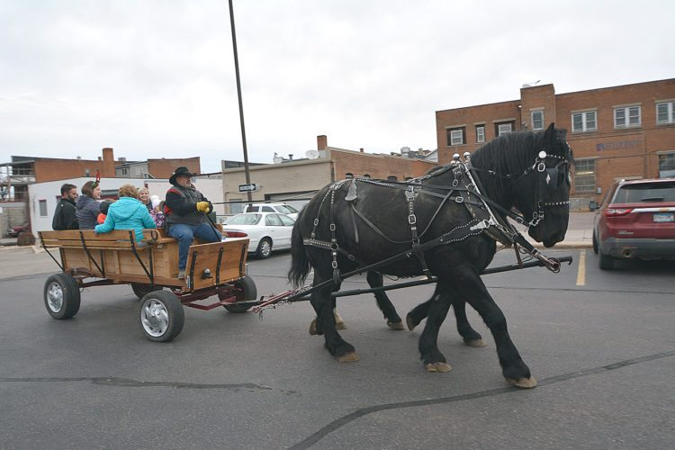 Jim Sutherland gave out wagon rides as part of United Prairie Bank's holiday open house Friday afternoon. Guests could visit the bank for some treats and to talk to Santa before jumping on board for a ride along Minnesota Street.