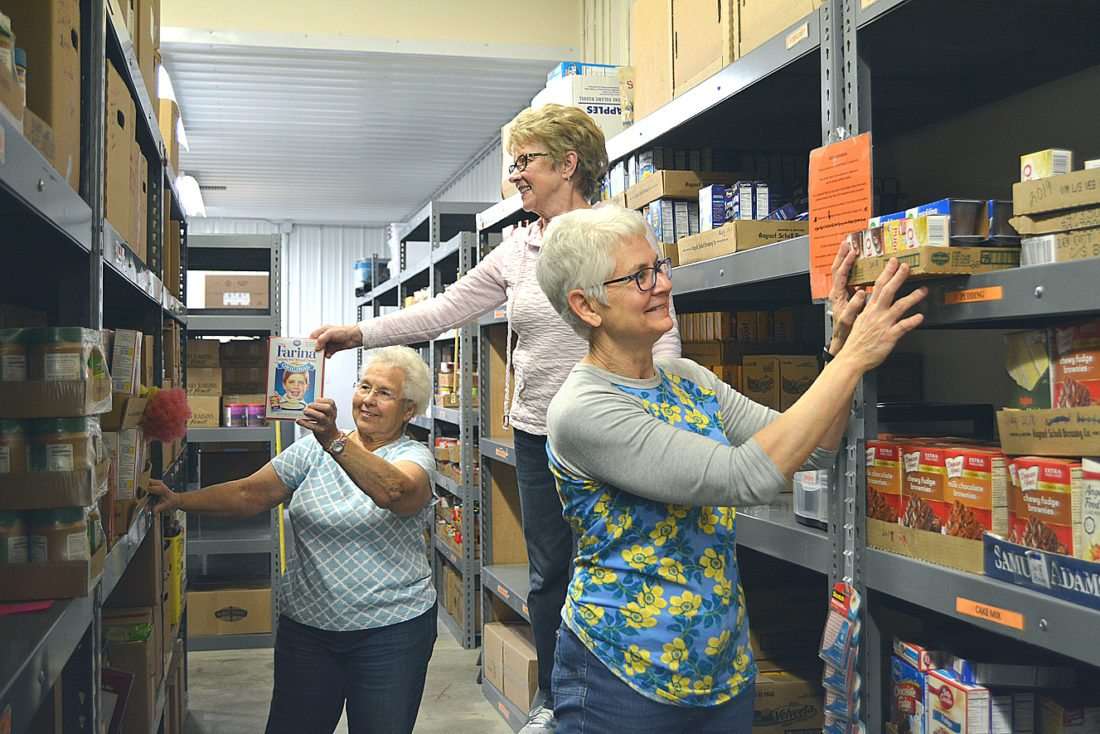 Staff photo by Connor Cummiskey Much of the food at the food shelf is stored on large metal shelves. Volunteers Carol Muller, left, Sue Liesch, middle, and Jackie Roesch, right, stock food on the shelves.