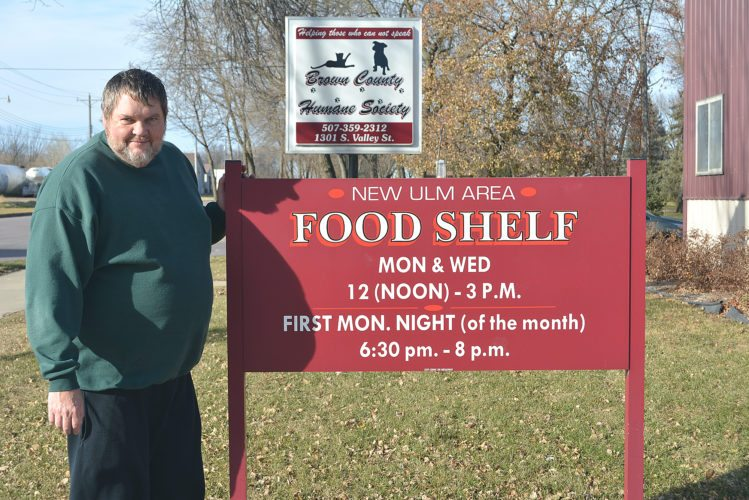 Staff photo by Connor Cummiskey Executive Director Brad Kirk stands next to the Food Shelf sign at 1305 S. Valley Street. The New Ulm Area Emergency Food Shelf offers low-income families monthly rations of staple foods to help make ends meet.