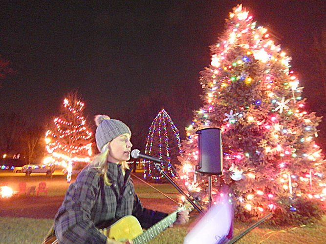 Oakwood Church lit its big Christmas tree as part of the opening of Winter Wonderland, Dec. 3. The event included horse-drawn carriage rides, soup, games, caroling and s'mores with fire. Pictured, singer Andes Lyn.  Staff photo by Fritz Busch