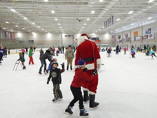 Staff photos by Fritz Busch  Children and parents skate with Santa and New Ulm Steel hockey players to holiday music at the New Ulm Civic Center Dec. 3. Participants skated free, decorated holiday treats, made crafts and other things with a non-perishable food donation.