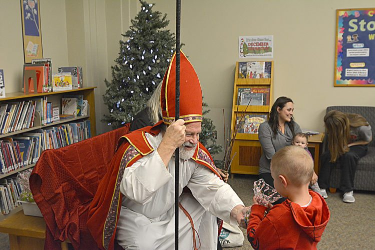 Staff photo by Connor Cummiskey  St. Nikolaus gives Hank Kirschstein, 4, a bag of candy after speaking to him about the meaning of Christmas. Nikolaus and Krampus appeared at the public library Tuesday evening, St. Nikolaus Day Eve, during the St. Nikolaus Storytime and Craft Event.