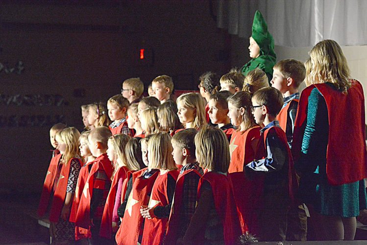 """First-graders sing """"Let Your Light Shine Out"""" along with the Christmas tree (Margo Finstad) about how Christmas would be dark without Jesus Christ. This was one of the lessons portrayed in """"It's a Wonder-Full Life,"""" the show put on by St. Anthony Elementary students Thursday as their Christmas program.   Staff photo by Connor Cummiskey"""