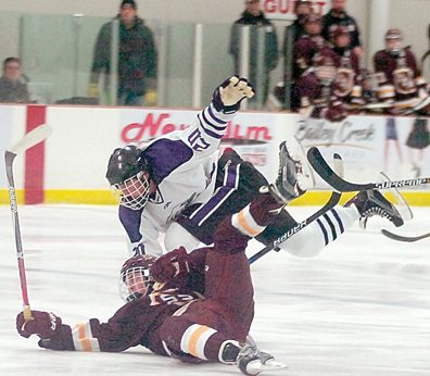 Staff photo by Steve Muscatello New Ulm's Kyle Tauer gets tangles up with a South St. Paul player during the second period Friday a the New Ulm Civic Center. For more photos of this event go to cu.nujournal.com