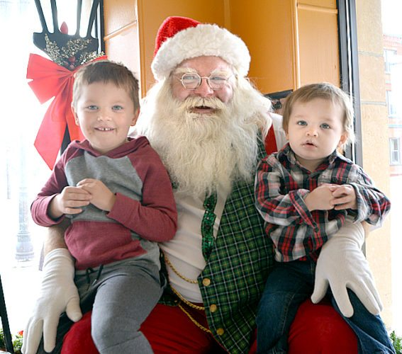 Staff photo by Connor Cummiskey Santa visited The Backerei Saturday. Jack Homan, 4, (left) and Noah Homan, 2, (right) sit on his lap as he asks them what they want for Christmas.