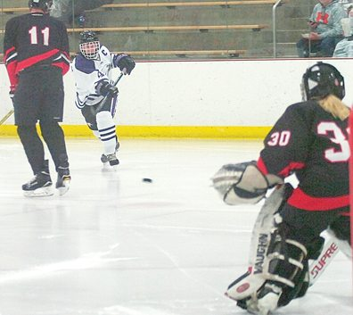 Staff photo by Steve Muscatello New Ulm's Luke Scheid launches a shot on goal as Matthew Muetzel (11) and Kia Jacobson of Redwood Valley look on during the second period Tuesday at the New Ulm Civic Center. For more photos of this event go to cu.nujournal.com