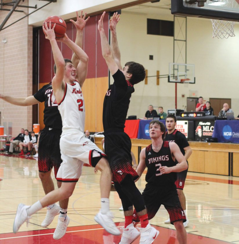 Staff photo by Travis Rosenau MLC's Ian Paulsen (21) attacks the bucket against a swarm of Bethany Lutheran defenders in Wednesday's UMAC matchup at MLC.