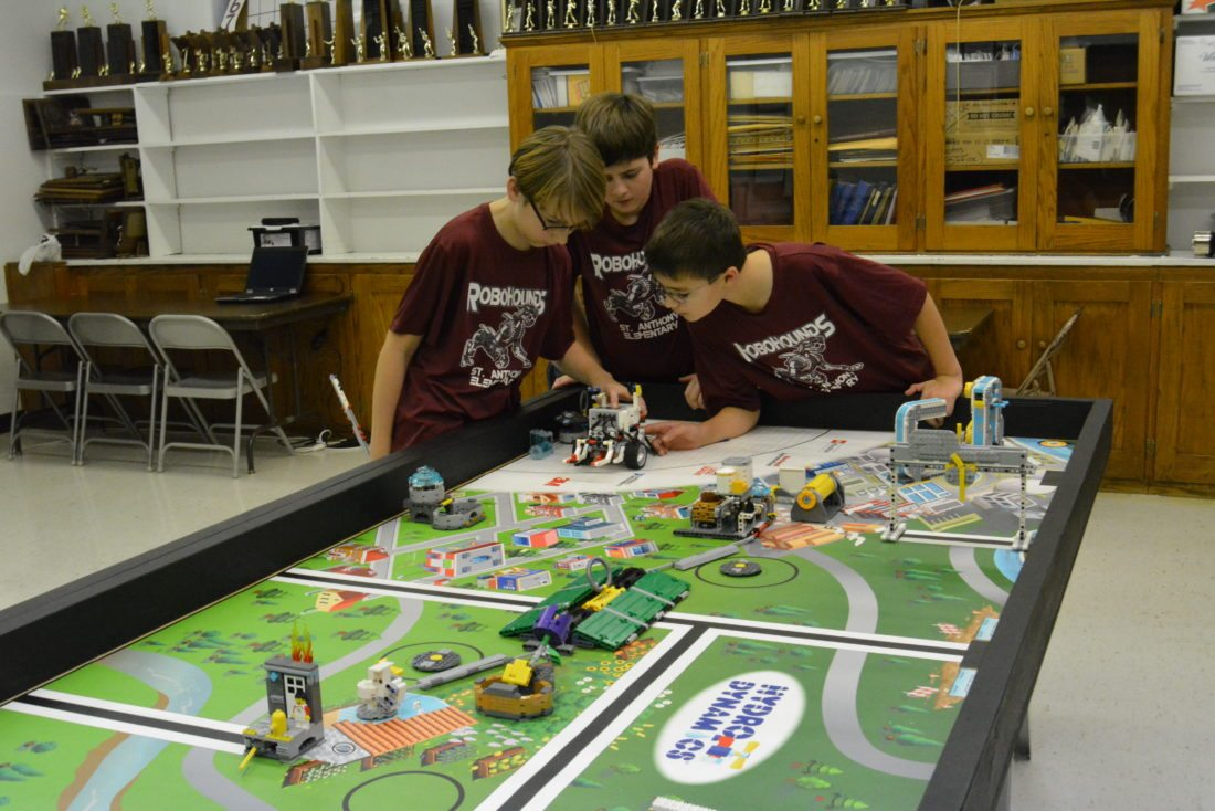 """Staff photo by Connor Cummiskey  Elliot Hoffman, left, Landon Klawitter, middle, and Zach Paszkiewicz, right, troubleshoot their robot """"The Candy Van"""" during an open house for the Robohounds Wednesday."""