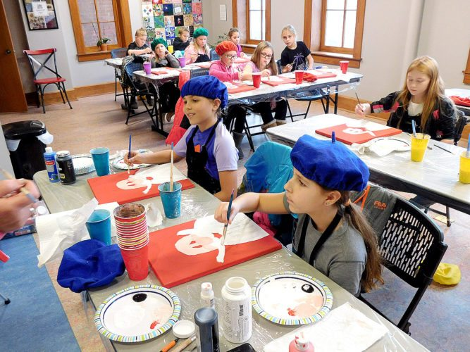 Staff photo by Clay Schuldt Above: In their matching blue painter's berets, sisters Lexi (left) and Payton (right) Fluegge and 17 other students learn paint Santa Claus at the Grand Center for Arts &Culture.