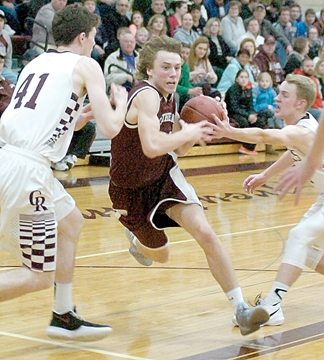 Staff photo by Steve Muscatello New Ulm Cathedral's Alex Hillesheim drives between a pair of Norwood-Young America defenders as he drives to the basket during the first half Monday at CHS. For more photos of this event go to cu.nujournal.com