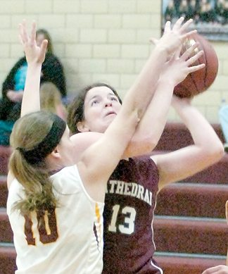 Staff photo by Steve Muscatello New Ulm Cathedral's Jenna Helget (13) tries to take a shot as Taylor Ebert of Lester Prairie/Holy Trinity defends during the second half Tuesday at CHS. For more photos of this event go to cu.nujournal.com