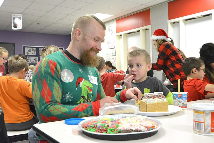 Jeff Toomer, left, and his son Leeroy, 5, make a gingerbread house at the Washington Learning Center. The annual event is held to engage parents of kindergarteners and give them some time to build the houses out of donated materials.