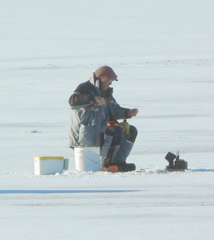 A man ice fishes on Sleepy Eye Lake Friday afternoon. A number of ice fishing houses and people fishing in the open could be seen on the lake.