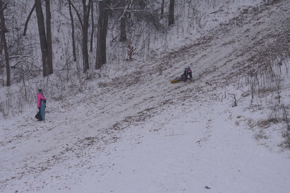 Staff photo by Connor Cummiskey  Two kids enjoy the fresh snow that fell on New Ulm Thursday by sledding down the hill between Harman Park and Hermann Heights.