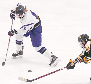 Staff photo by Steve Muscatello New Ulm's Ali Beltz gets the puck away from a Mankato East/Loyola player during the first period Tuesday at the New Ulm Civic Center. For more photos of this event go to cu.nujournal.com
