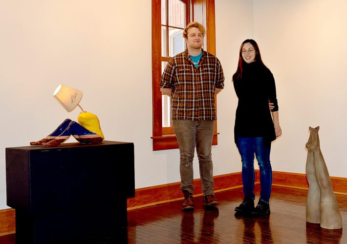 "Josh Schutz, left, and Hanna Newman, right, stand between two sculptures in their show ""Beatniks."" On the left is Schutz's ""Die, Cry, Hate"" and on the right is Newman's ""Dive."" (Photo by Connor Cummiskey)"