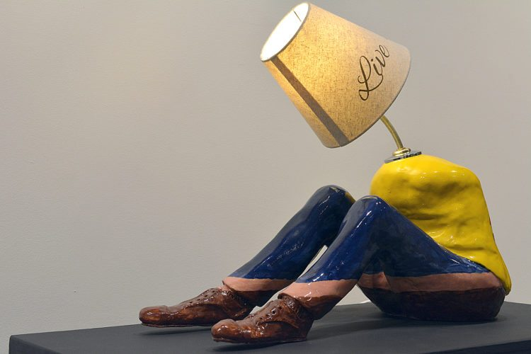 """Cry, Die, Hate"" by Josh Schutz, mixed media. The name, which references the ""Live, Love, Laugh"" written on the lampshade is marked out in colors on the back of the torso."