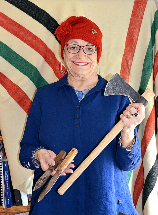 Staff photo by Connor Cummiskey Executive Director Kathleen Backer wears a traditional hat and holds two knives and a hatchet that traders would have given to the Native Americans in exchange for pelts.