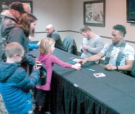 Staff photo by Steve Muscatello Minnesota Twins players Robbie Grossman (center) and Jorge Polanco (right) sign autographs for Kate and Isaak Brand during the Winter Caravan stop Monday at the Best Western Blus in New Ulm. In the background is broadcaster Corey Provus is pictured in the background at left. For more photos of this event go to cu.nujournal.com