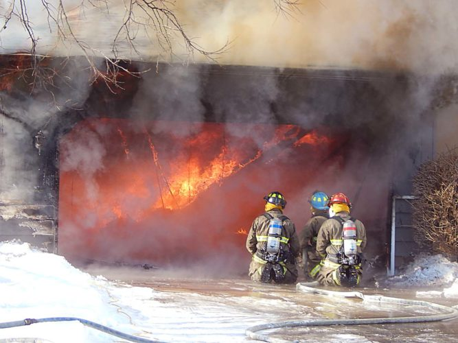 Staff photo by Fritz Busch New Ulm firefighters battle a garage engulfed with flames at 209 S. State Friday.
