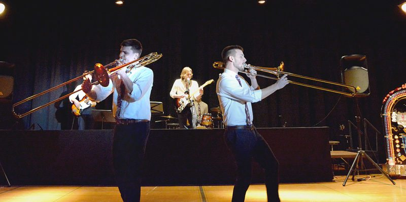 """Dan Wessel, left, and Justin Steinke jammed on their trombones out front during The Futons' rendition of """"Brown Eyed Girl"""" by Van Morrison. The Futons were the featured band at State Street Theater's Date Night for the Decades, musical revue Friday and Saturday"""