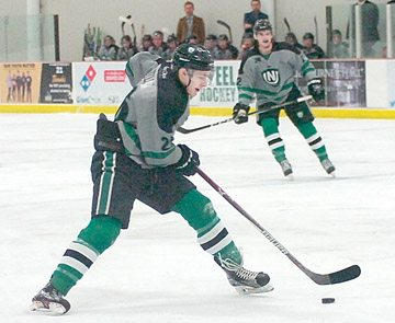 File photo by Steve Muscatello New Ulm Steel forward Tom Reilly tries to make a move with the puck as teammate Bayler Kraus (background on the ice) looks on during a recent Steel game at the New Ulm Civic Center.