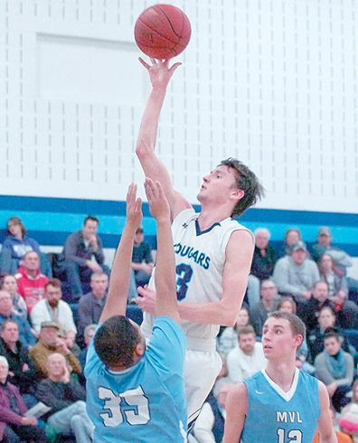 Staff photo by Steve Muscatello Cedar Mountain/Comfrey's Dylan Hillesheim takes a shot as Minnesota Valley Lutheran's TaShawn Parker (35) defends and Jake Kettner looks on during the first half Monday at MVL. For more photos of this event go to cu.nujournal.com