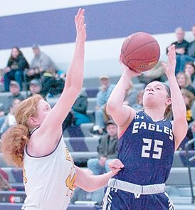 Staff photo by Steve Muscatello New Ulm's Iyanna Wieland (25) takes a shot as Emily Eckheart of Mankato East defends during the second half Monday at New Ulm High School. For more photos of this event go to cu.nujournal.com