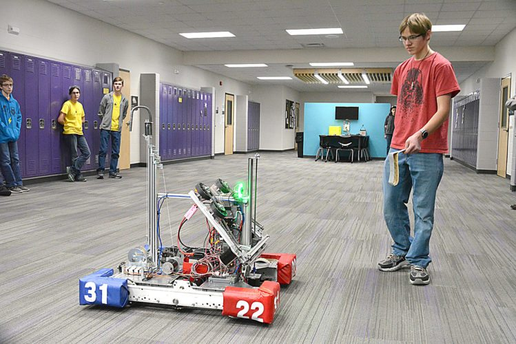 Staff photo by Connor Cummiskey  Alluminator member Trenton Beranek leads the team's robot around with a reflector strip as a demonstration of the robotics team at the high school during a school board study session.