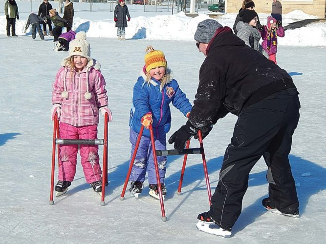 """Isabella, left, and Adeline Hoffmann learn to skate with some help from their father Sam Hoffmann of New Ulm at Harman Park Saturday. They were part of the crowd celebrating the New Ulm Park & Recreation's """"Snow Day"""" at the park with skating, horse-drawn sleigh rides, hot cocoa and s'mores."""