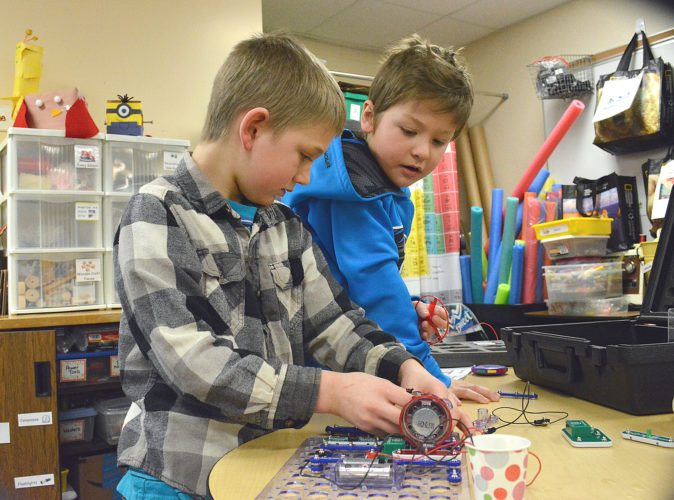 Staff photo by Connor Cummiskey Second-graders Jacob Pornter, left, and Brenton Nachreiner, right, use snap circuits to manipulate electrical flows and connect a switch to a spinning fan blade to shut it off.