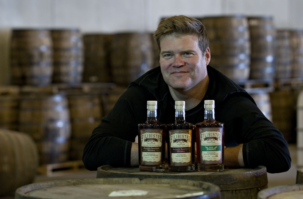 Rob Moulthrop, sales manger for Filibuster Bourbon Distillery, shows off the company's three brands of whiskey at the Maurertown facility.  Rich Cooley/Daily