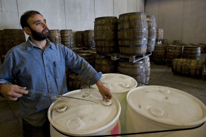Sid Dilawri, master blender for Filibuster Bourbon Distillery,  siphons gin blended at the Maurertown facility.  Rich Cooley/Daily