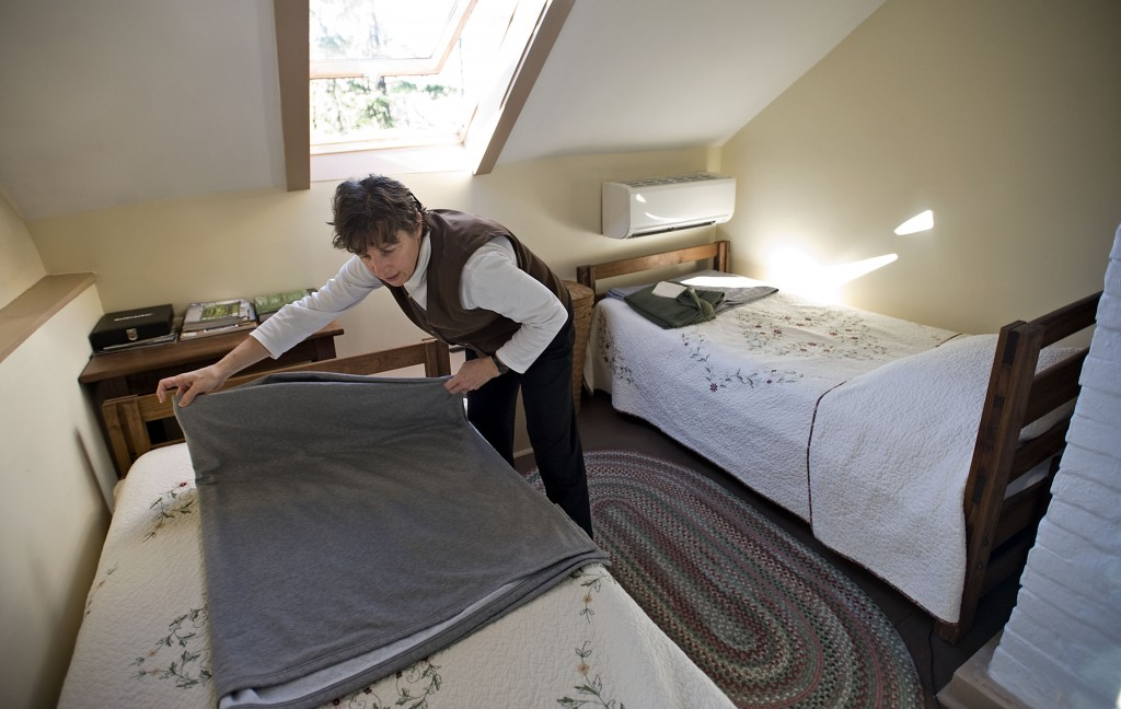 Lisa Jenkins, an owner of Mountain Home Bed and Breakfast, makes a bed in this cabin that she and her husband Scott own near the trailhead south of Front Royal. The town and county are looking for ways to become more hiker friendly for those on the Appalachian Trail. Rich Cooley/Daily