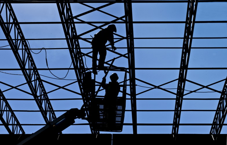A pair of welders work on the roof of this warehouse under construction at Valley Fertilizer in Mt. Jackson. The 80,000 square foot building is being constructed by Harman Construction, Inc. of Harrisonburg. Rich Cooley/Daily