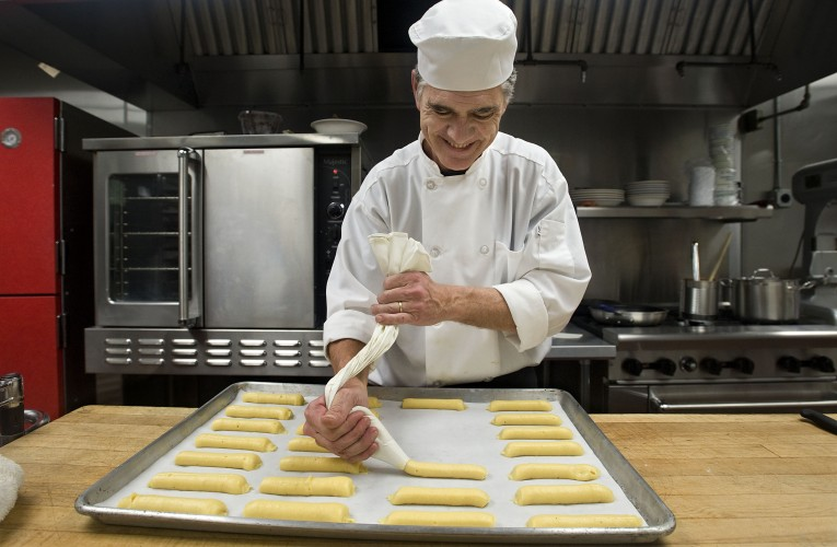 Francois Martin,  chef and co-owner of Bon Matin chez Leroy, presses eclairs on this tray inside the new French bakery on East Boscawen Street in Winchester. Rich Cooley/Daily