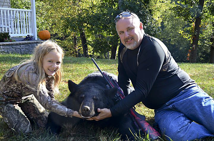Woodstock's Ella Emmons, 8,  and David Brock pose with a black bear Emmons harvested on youth day on Sept 27. She shot this 240-pound black bear on National Forest land in Zepp.   Courtesy photo