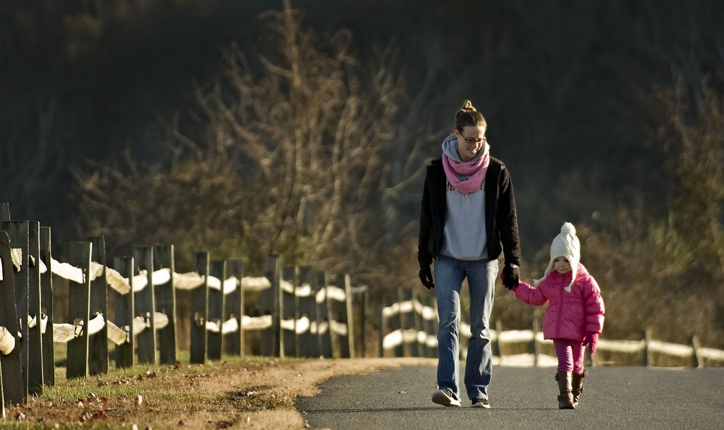 Lauren Himelright and her daughter Sophia Ritter, 2, of Strasburg, walk along this line of fencing on Park Avenue in Strasburg on a cold fall afternoon.   Rich Cooley/Daily