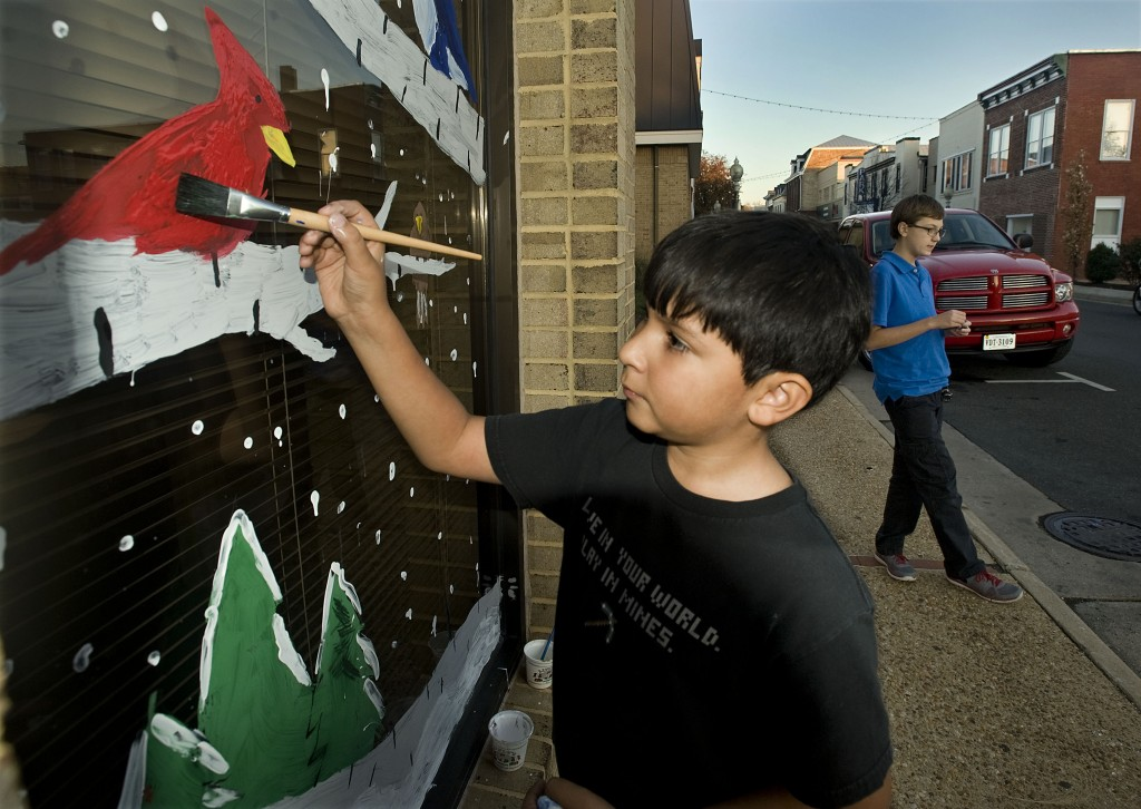 Oscar Martinez, 10, of Front Royal, decks Front Royal's Town Hall outside Main Street on Monday afternoon. Martinez and about 20 other students from E. Wilson Morrison Elementary helped to decorate the windows for the Christmas season. Rich Cooley/Daily