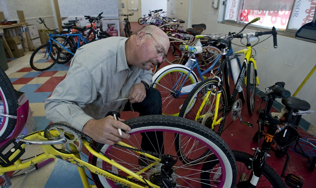Gary Bunch, of Stephens City, checks over one of the new bicycles that are among gifts donated or bought for Toys for Tots inside the Stephens City distribution center.  The Toys for Tots chapter serves Shenandoah, Warren, Frederick, Clarke and Page counties. Rich Cooley/Daily