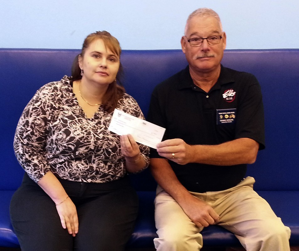 Michal Ashby, youth services supervisor for the children's section at the Samuels Public Library in Front Royal, left, accepts a check for $1,000 presented to the library by Dennis Henline, exalted ruler of the Front Royal Elks Lodge 2382. Courtesy photo