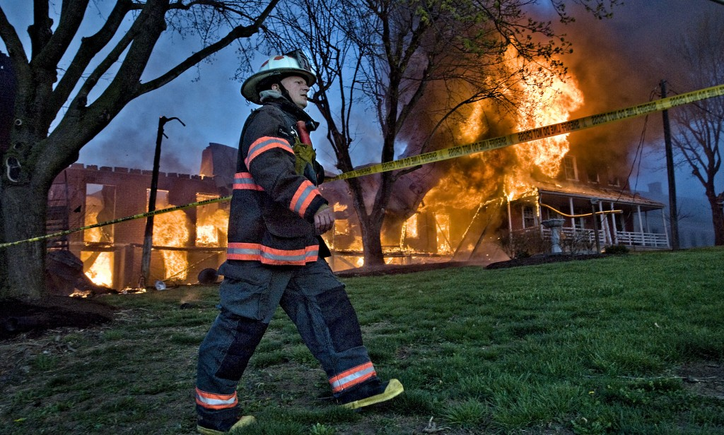 Shenandoah County Fire and Rescue training chief  Bill Streett tapes off the scene of the Shenandoah County Farm fire.   Rich Cooley/Daily file