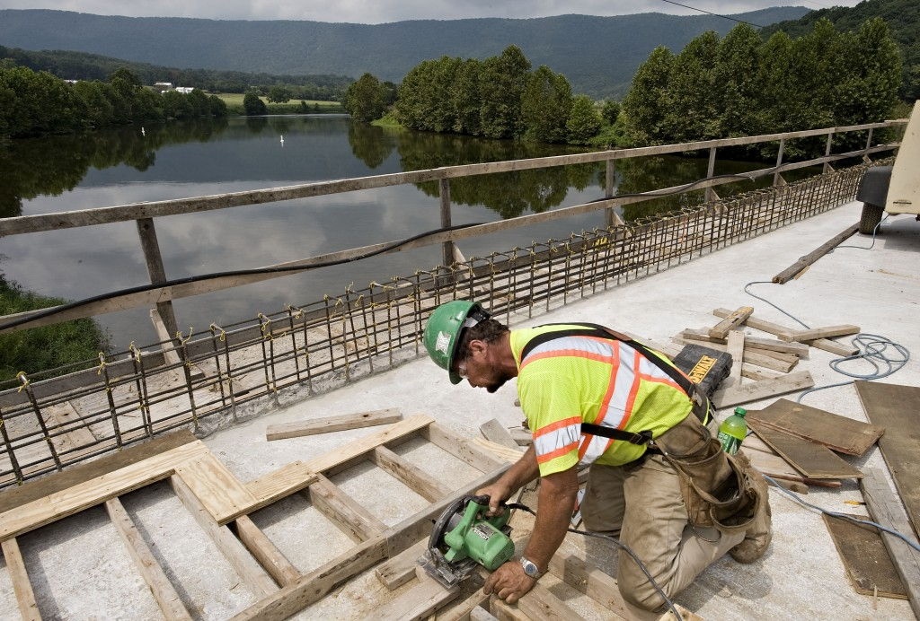 Clay Roop, a carpenter for Kanawha Stone Co, Inc. of Nitro, WV builds forms for the jersey walls of the new bridge under construction on Indian Hollow Road and the South Fork of the Shenandoah River near Bentonville.  The $4.4 million bridge is scheduled to be completed in mid-October.  Rich Cooley/Daily