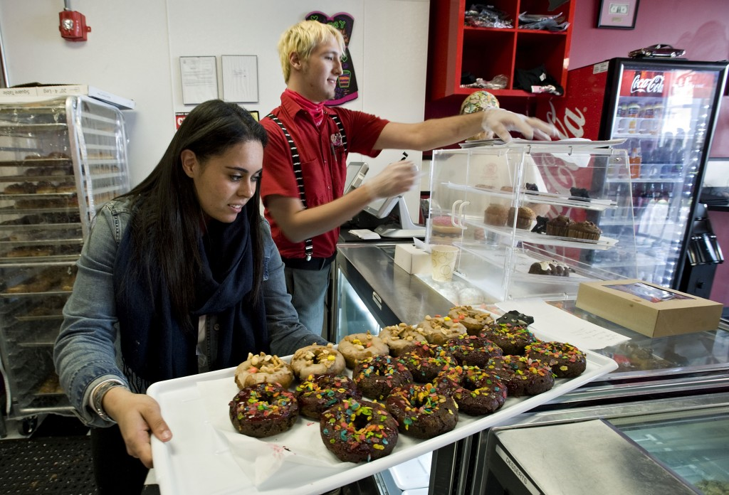 Tiana Ramos, 17, prepares to place  a tray of donuts into a display case inside Naughty Girls Bake Shop at Riverton Commons in Front Royal. The business is expanding into Northern Virginia. Rich Cooley/Daily file