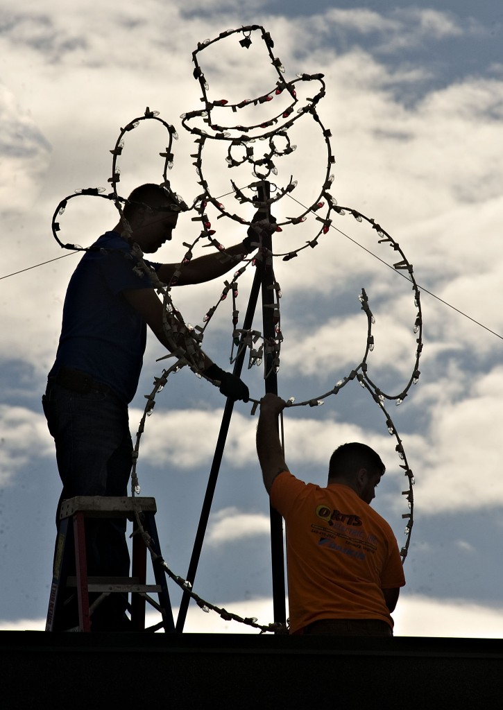Allen Gochenour, lead electrician for Ortts Electric Service in Edinburg, left, and his helper Josh Giouard, right, install this snowman on top of the Woodstock Shopping Center on Monday as a storm system starts to move in. Rich Cooley/Daily